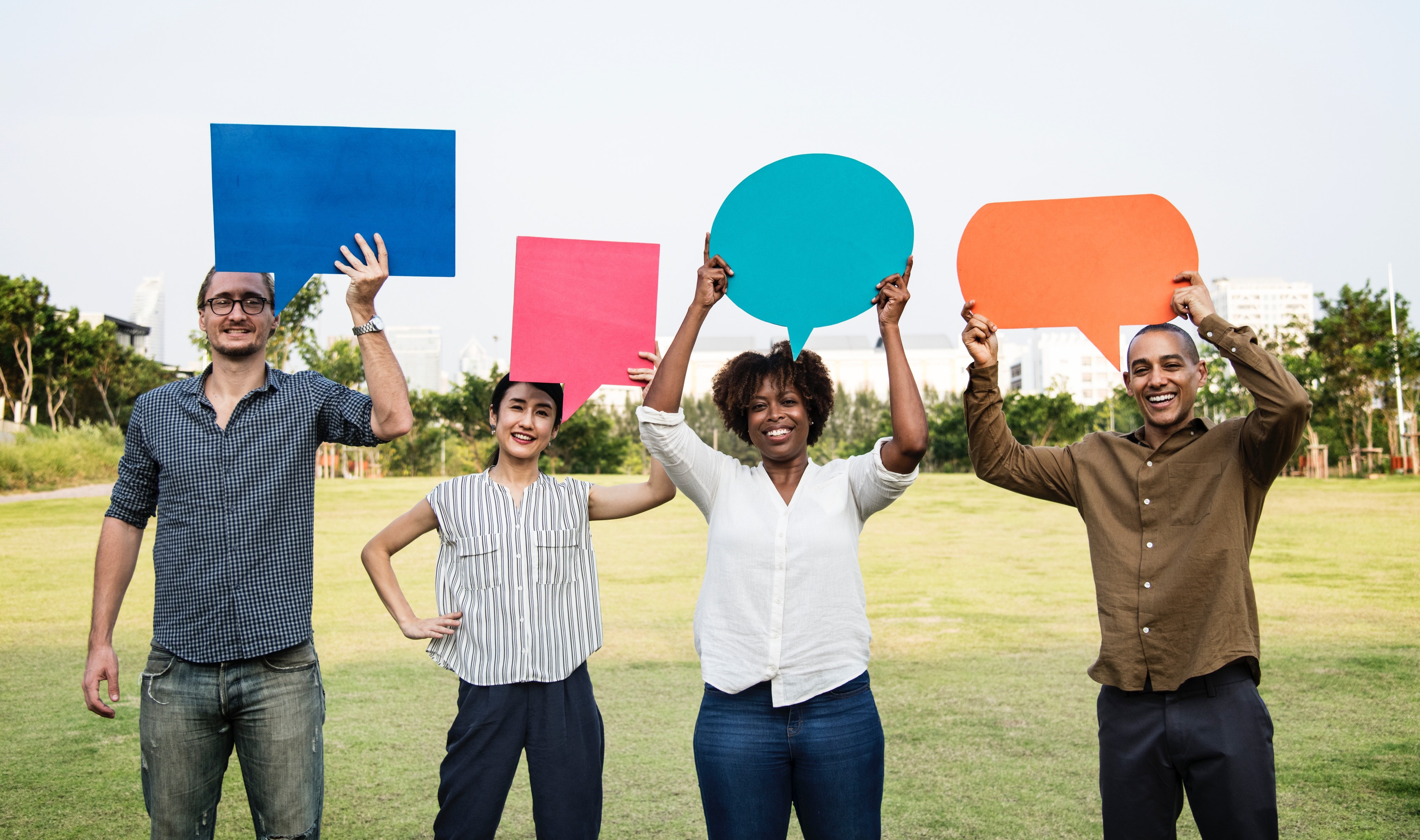 Group of four people holding speech bubbles