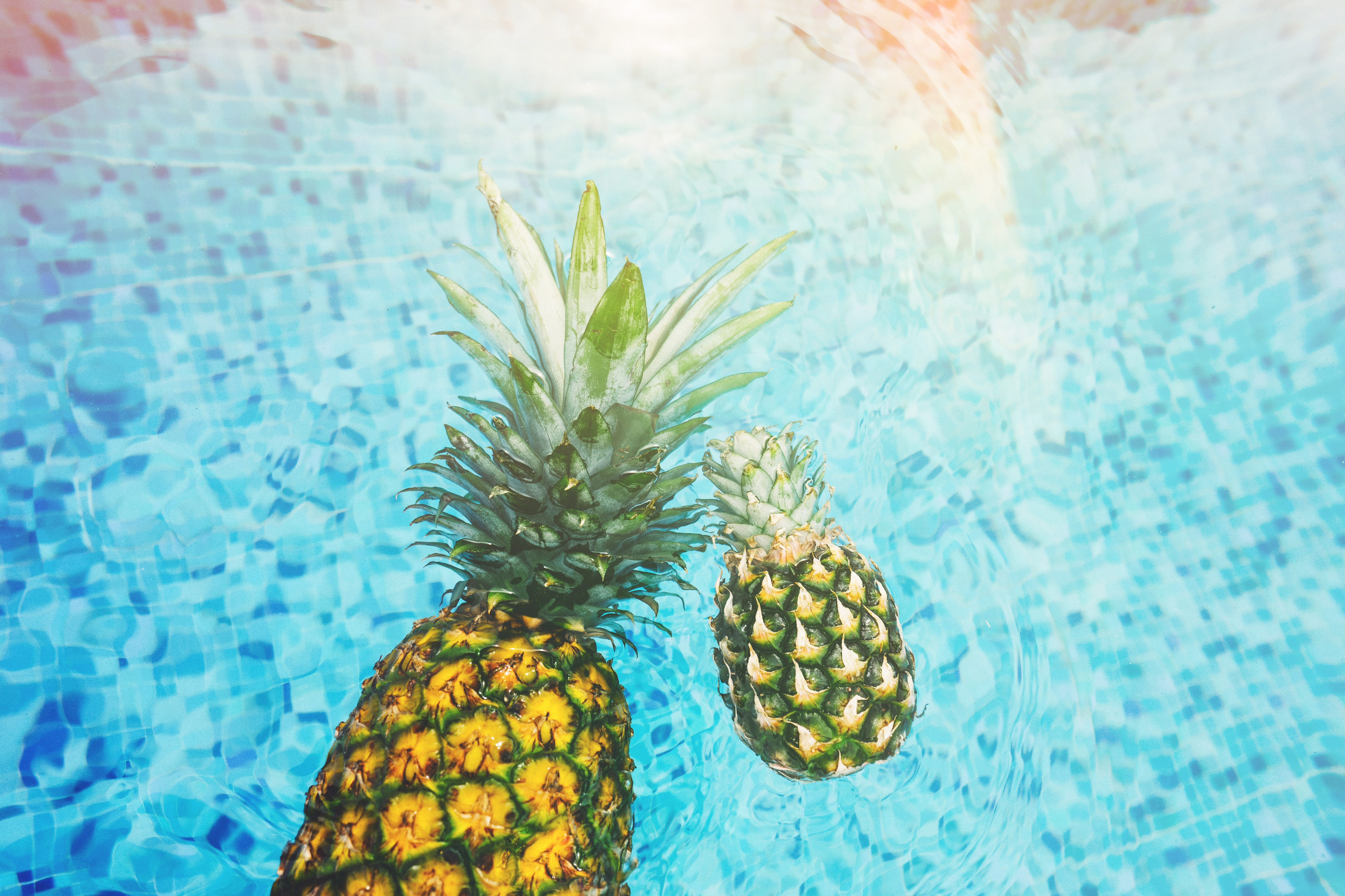 Two pineapples floating in a pool