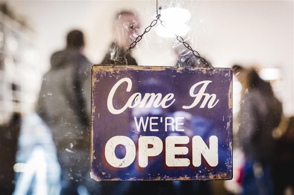 An open sign facing outwards from behind a glass door