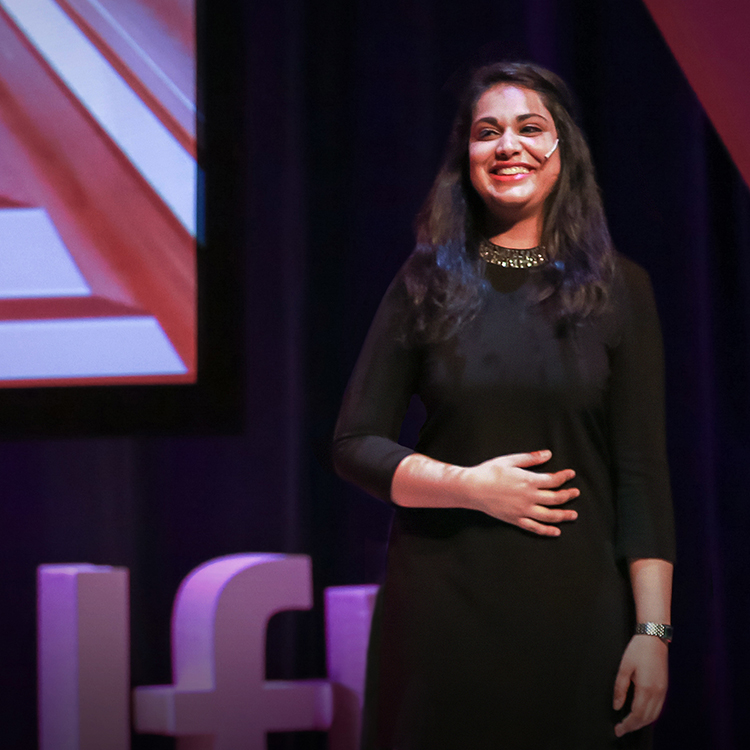 Mileha Soneji speaking on stage giving TED talk