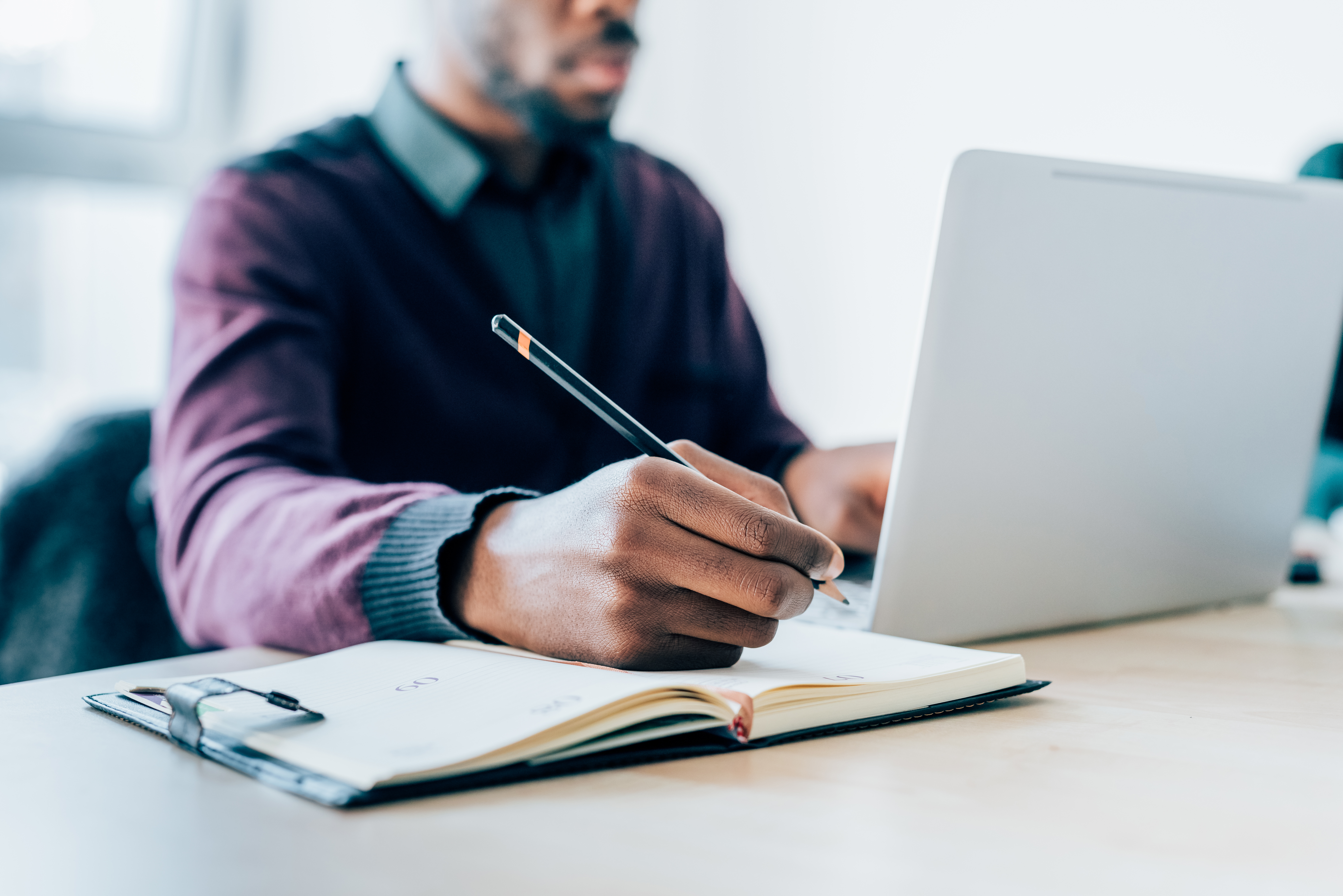 Person writing in notebook while working on laptop in office