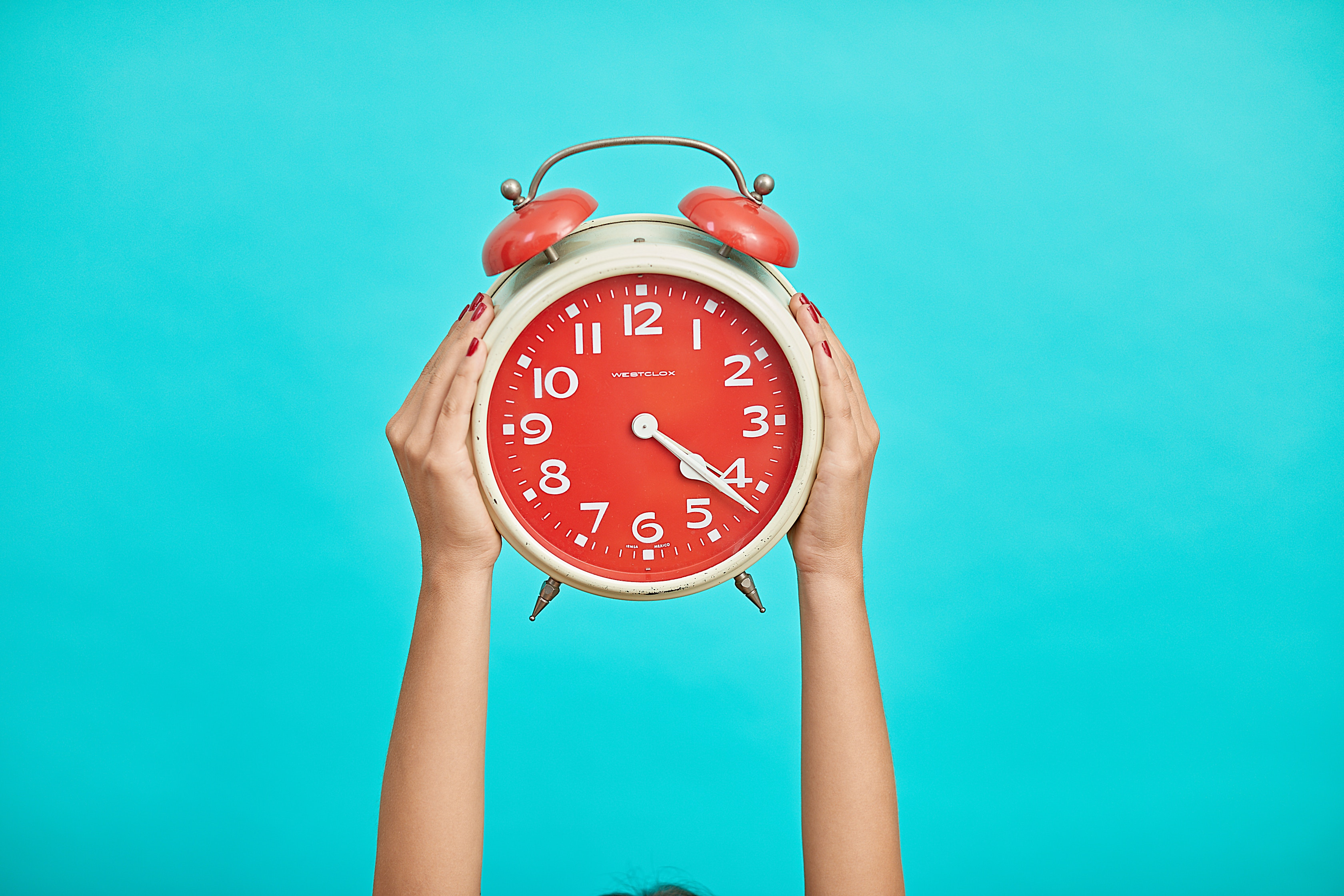 Person holding red alarm clock on blue background